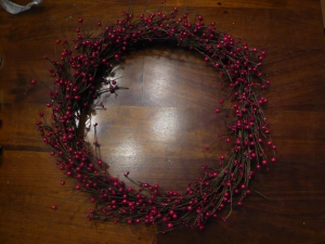 Berry garland wrapped into the shape of a wreath and secured with wire.