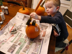 I used a thin brush to paint glue around the pumpkin's stem and let E do the rest.